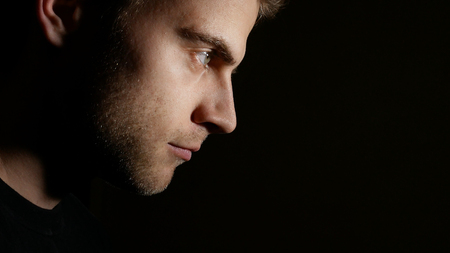 profile portrait of a man on a black background