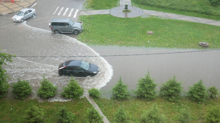 the car rides through puddles during the rain, a bad road, water after heavy rains Фото со стока