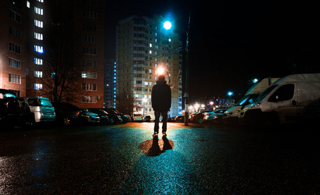 a mysterious man stands alone in the street, among cars in an empty city, weat road after the rain, walks the night street, dreams