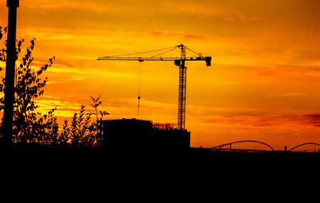 crane and building silhouettes over sun at sunset in summer