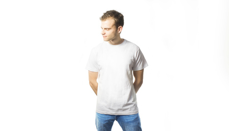 the guy in the blank white t-shirt, stand, smiling on a white background, mock up, free space,  design, template for design print Фото со стока