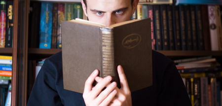 man reading a book on the background of books in the library, focus on the eyes 写真素材
