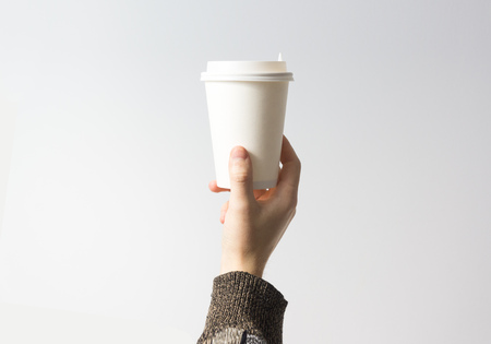 Hand holding a mug,  Paper Coffee Cup  with delicious coffee in a cafe on a white background, mock up, blank, your cafe shop design 写真素材