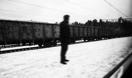 unknown person silhouette of a strange mystic man, standing on the street, at the background of freight train wagons 写真素材
