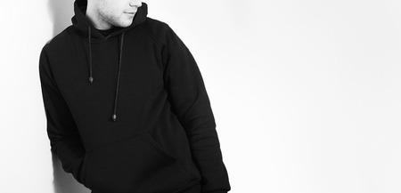 the guy in the Blank black hoodie, sweatshirt, stand, smiling on a white background, mock up, free space, template for print, plain hoody design