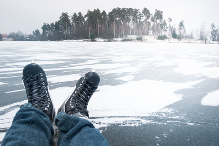 man in ice skates a crystal clear frozen lake in winter, sprinkled with snow