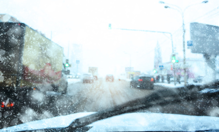 snowy road, blurred background, snow and water on the car window