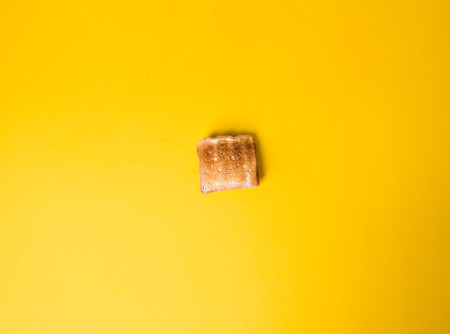 scalded toasted piece of bread toast on a yellow background, flat style, Фото со стока