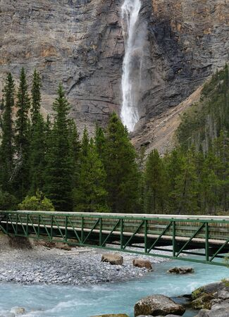 Takakkaw Falls In Yoho National Park With A Wooden Bridge Over Yoho River In The Foreground