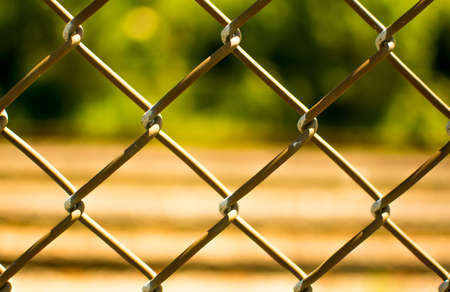 Closeup of a fence with a blurred rail background Stock Photo