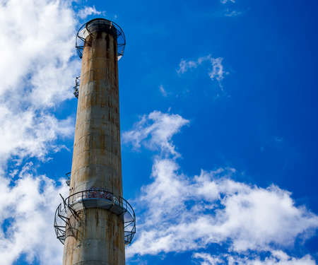 Industrial chimney with a blue sky background Stock Photo