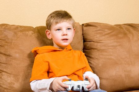 couches: Here is a photo of a young boy sitting on a couch playing a video game.