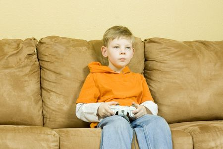 Young boy sitting on couch playing a game