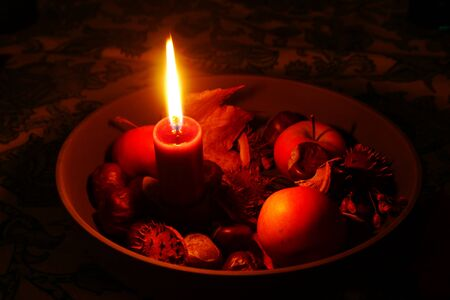 Red burning candle in a bowl with chestnuts, apples and foliage