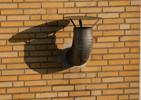 Ventilation opening on a brick wall with shadows