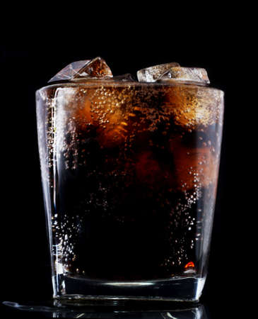 Dark tone cool soft drink cola carbonated in glass with ice on black background. summer drink and refreshing