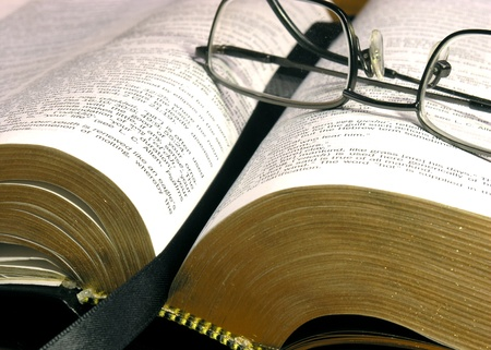 An open bible with reading glasses on top   Bible version is open source NET version Stock Photo