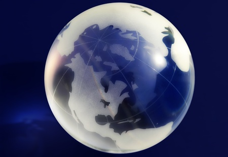 A glass globe on a blue background, lit from above