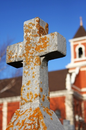 A stone cross grave stone, covered in moss, and lichens with a church in the background   The sky is bright blue  Stock Photo