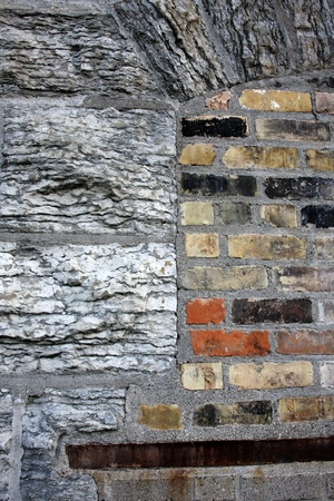 Large granite bricks, mixed with standard clay bricks on an old abandoned industrial building, downtown Minneapolis, MN
