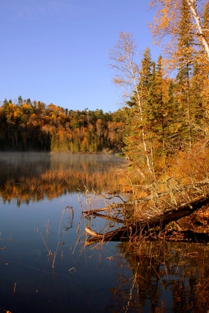 A morning vista of Bearskin lake during the fall season   fog shrowds the lake, while reflections on the very still water accent the seasonal color  Stock Photo
