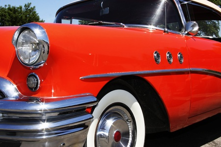 hubcap: An old antique 1950 buick hot rod   Shiny orange, with lots of chrome   Great collectors car