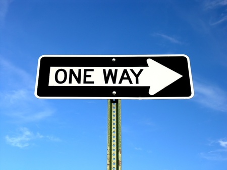 A one way sign on a blue sky