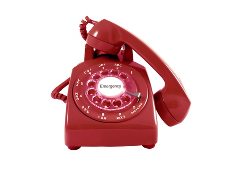 A red retro rotary phone isolated on white   Emergency text in the center of the dial        Stock Photo