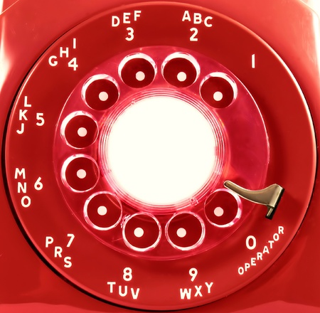 A rotary phone dial, in red   Room for copy on the center of the dial