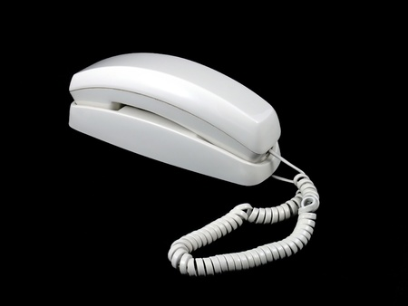 An old corded phone isolated on a black background Stock Photo