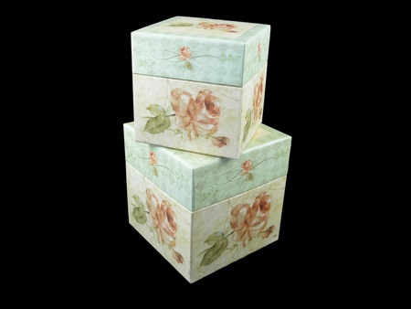 Decorative boxes stacked, with floral pattern   Isolated on black