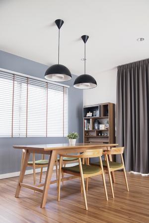 Mesa de comedor en acogedor comedor con ventana de persianas, decorada en estilo loft. Foto de archivo