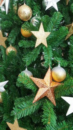 Christmas tree decorating with gold star snowflake and metallic balls, closeup