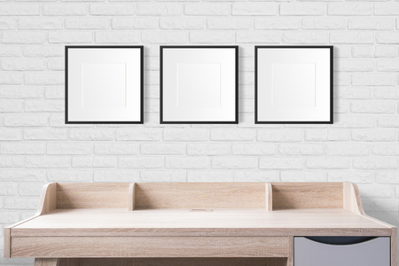 working table with blank frames in the empty studio with white brick wall.
