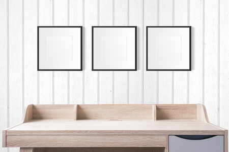 working table with blank photo frames in the empty studio with white wood wall.