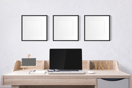 notebook computer and stationery on working table with blank photo frames in the studio with white cement wall. 版權商用圖片