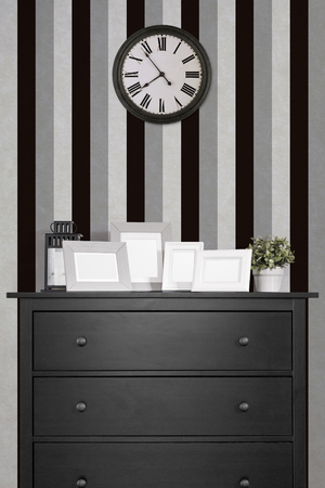 picture frames collages on black wooden cabinet and clock in empty room with black and white background, vintage style