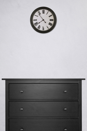 black wooden cabinet and clock in empty room with white cement wall. vintage style, black and white