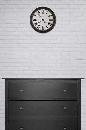 black wooden cabinet and clock in empty room with white brick wall background. vintage style, black and white 版權商用圖片