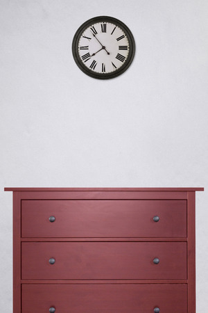 red wooden cabinet and clock in empty room with white cement wall background. vintage style