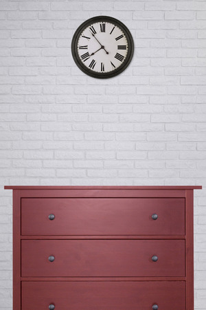 red wooden cabinet and clock in empty room with white brick wall background. vintage style