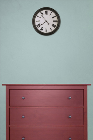 red wooden cabinet and clock in empty room with pastel green background. vintage style