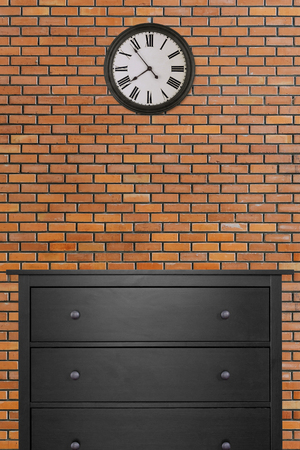 black wooden cabinet and clock in empty room with red brick wall background. loft style 版權商用圖片