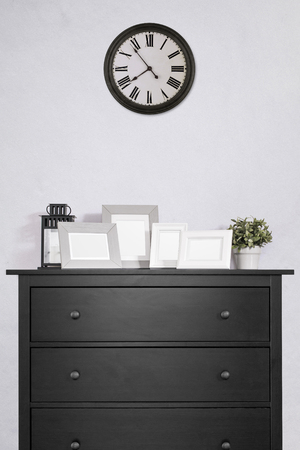 picture frames collages on black wooden cabinet and clock in empty room with white cement wall background, vintage style