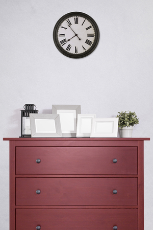 picture frames collages on red wooden cabinet and clock in empty room with white cement wall background, vintage style