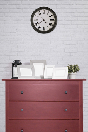 picture frames collages on red wooden cabinet and clock in empty room with white brick background, vintage style