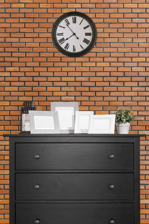 picture frames collages on black wooden cabinet and clock in empty room with red brick wall background, loft style 版權商用圖片