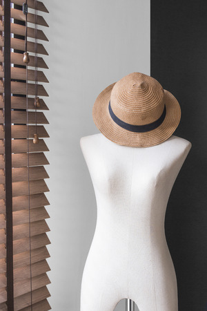 close up of mannequin dummy with pretty beautiful straw hat in cozy studio with black wall