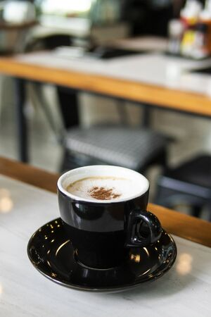 black coffee cup and hot cappuccino coffee on white wooden table. blur background 版權商用圖片