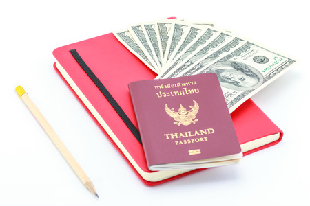 Passport and dollar on the book beside pencil. photo